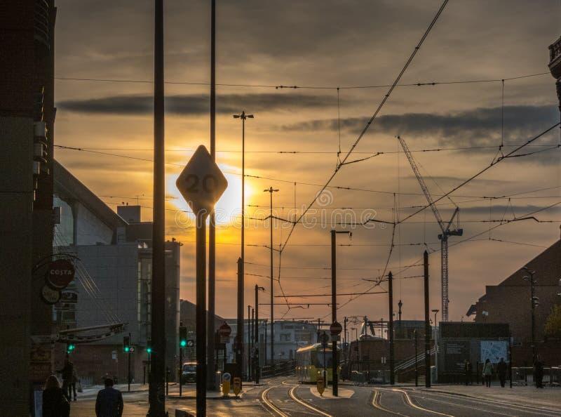 Spårvagn och tramlines i Manchester, UK, med inställningssol a arkivfoto