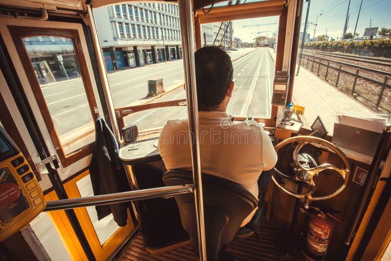 Spårvagnchaufför i kabin av det retro spårvägflyttningmedlet förbi moderna områden av huvudstaden royaltyfria bilder