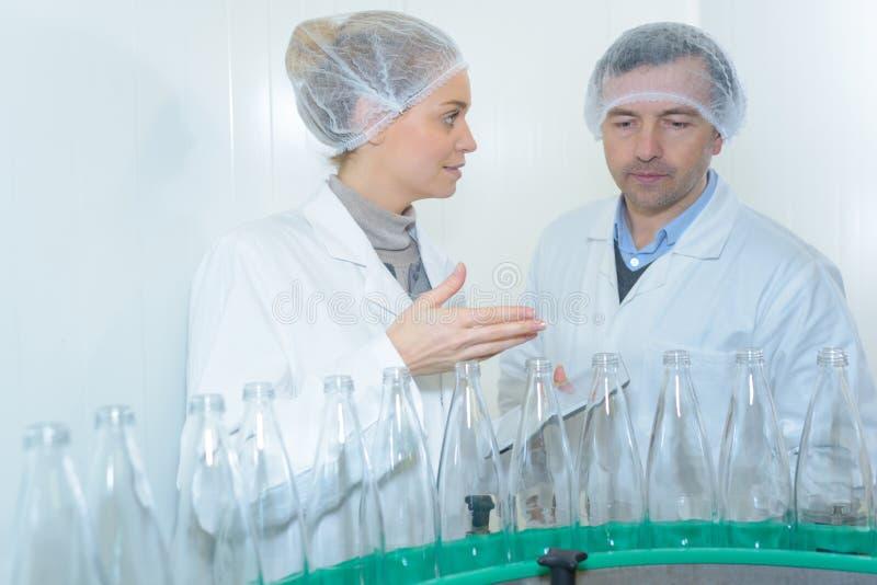 Spécialiste dans l'usine vérifiant des bouteilles photos libres de droits