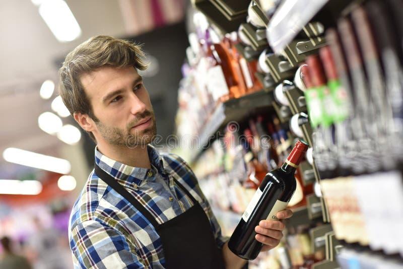 Spécialiste en vin travaillant au supermarché photos stock