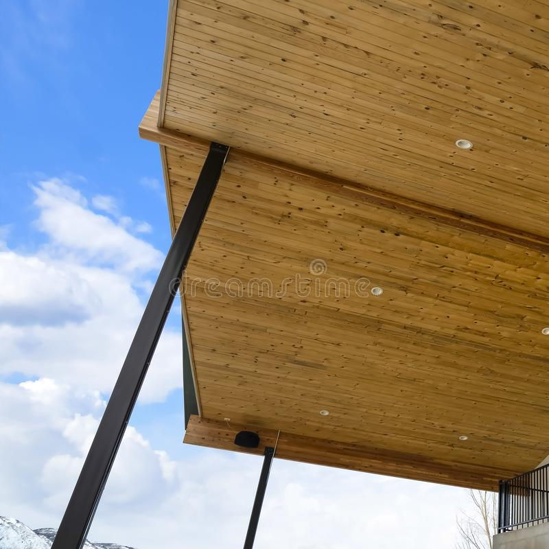 Spód dach z brąz drewnianymi deskami i round podsufitowymi światłami przeciw niebu fotografia stock