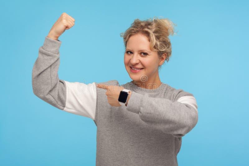 Spójrz na moją siłę Pewna, dorosła kobieta z krótkimi włosami w sportowej, przypadkowej bluzie wskazującej na biceps obraz stock