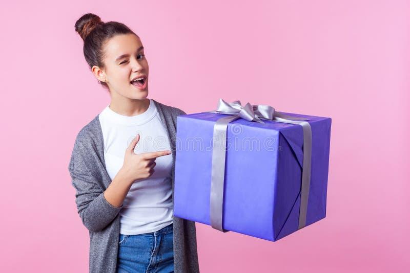 Spójrz na ten prezent Portret pięknej nastolatki, brunetki, wskazującej na pudełko z upominkami i mrugającej radośnie różowe tło fotografia royalty free