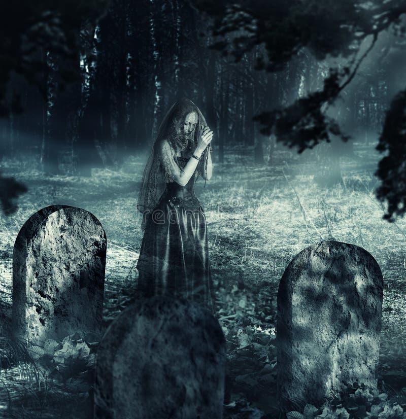 Spöke av kvinnan på nattkyrkogård royaltyfri foto