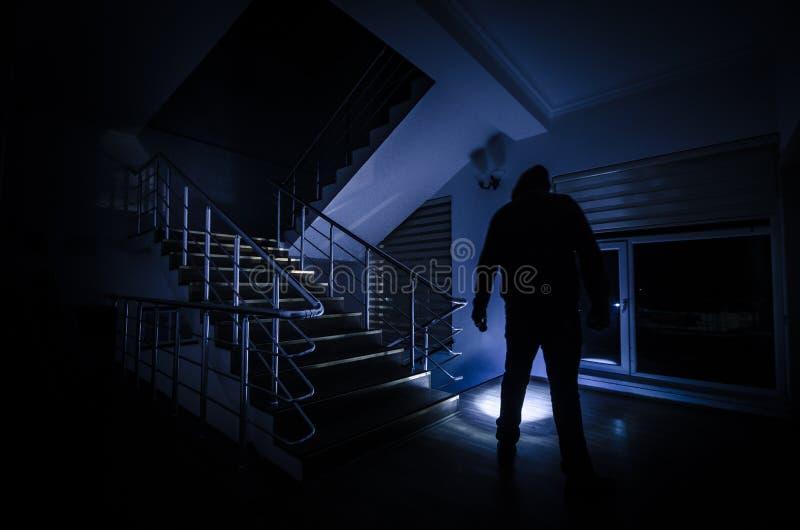 Spöke i det spökade huset på trappa, mystisk kontur av spökemannen med ljus på trappa, fasaplats av spöklik llig för läskig spöke fotografering för bildbyråer
