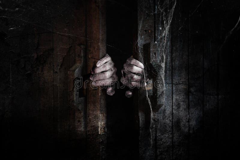 Spökehänder öppnar trädörren från insidan av det gamla mörka rummet royaltyfri bild