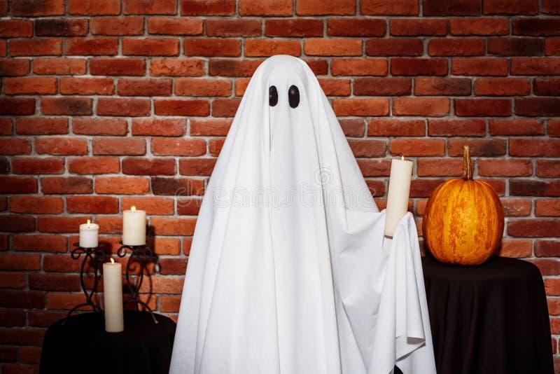 Spökeinnehavstearinljus över tegelstenbakgrund Halloween deltagare arkivbild