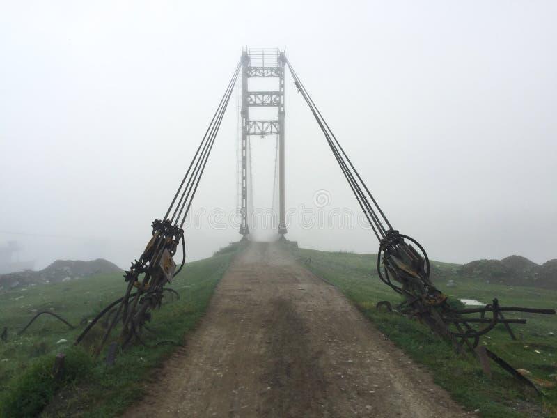 Sp?klik gammal ing?ng f?r upph?ngningbro till dimman Altai bybro Tidig dimmig morgon fotografering för bildbyråer