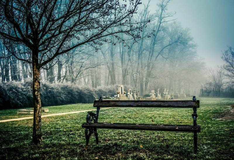 Spöklik kyrkogård i dimma royaltyfria bilder