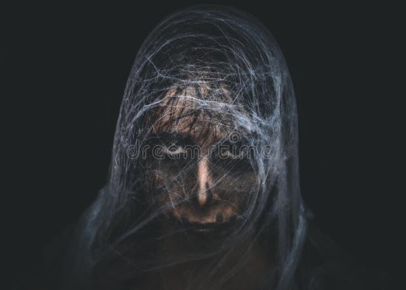 Spöklikt tecken som täckas med spiderweb på svart bakgrund arkivfoton