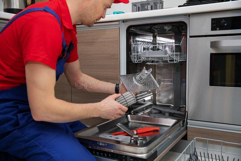 Spülmaschinenwartungsservice - Schlosser, der Nahrungsmittelrückstandfilter überprüft stockfotografie