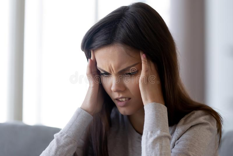 Spęczenie stresujący się młodej kobiety uczucia bólu migreny silny pojęcie zdjęcia stock
