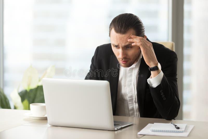 Spęczenie wprawiać w zakłopotanie biznesmena patrzeje laptopu ekran przy miejscem pracy obraz stock