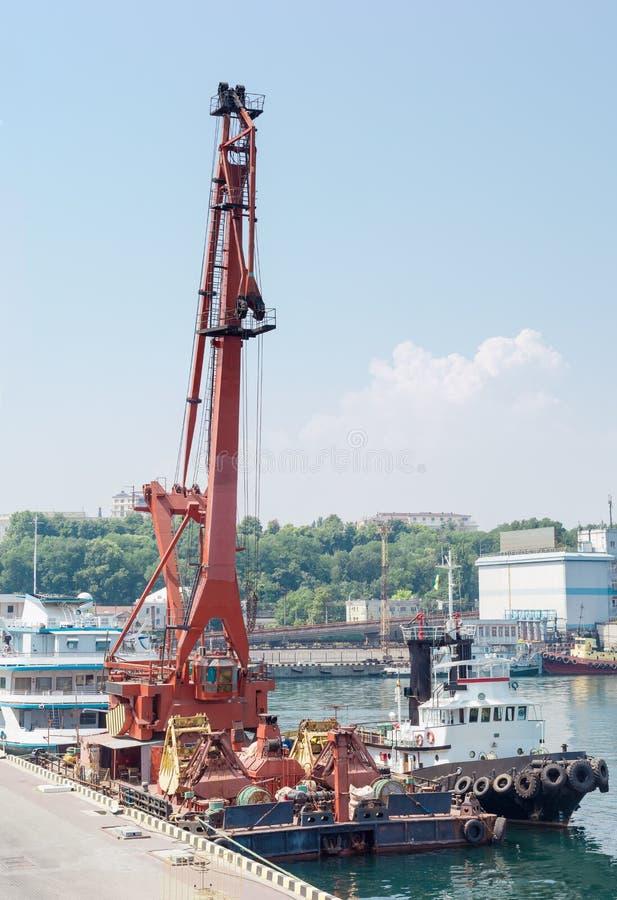 Spławowy żuraw i morski holownik przy port morski kuszetką fotografia stock