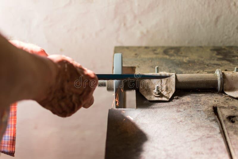 Sp?cialiste plus ?g? affilant le couteau en acier sur le tour de roue photo libre de droits