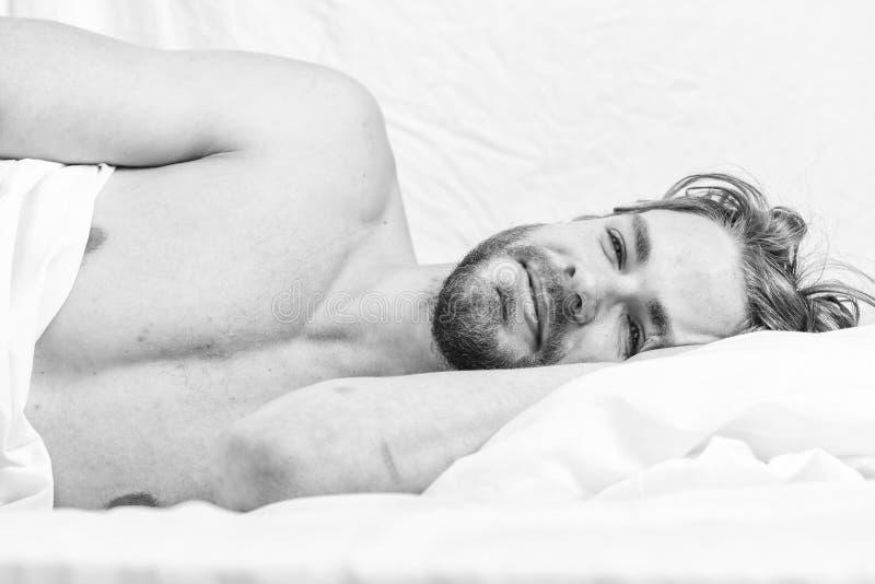 Sp?ter Vormittag verschlafen H?bscher Kerl des Mannes gelegt in Bett am Morgen Spitzen auf, wie man das F?hlen frisch und Energie lizenzfreie stockbilder