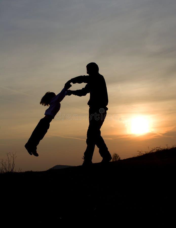 Spaß des Vaters und des Kindes im Sonnenuntergang lizenzfreies stockfoto