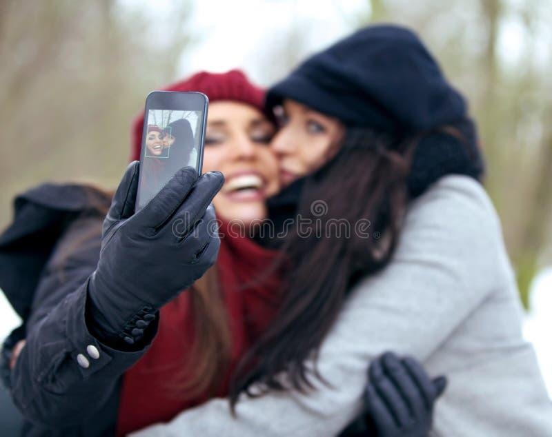 Spaß-Frauen, die draußen Fotos mit einem intelligenten Telefon machen stockfoto