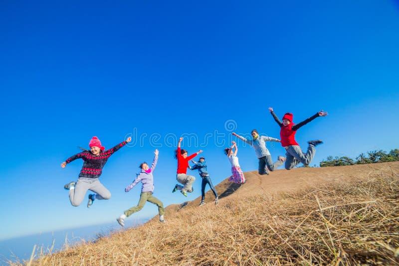 Spaß-Gruppe junge Leute, die draußen springen stockbild