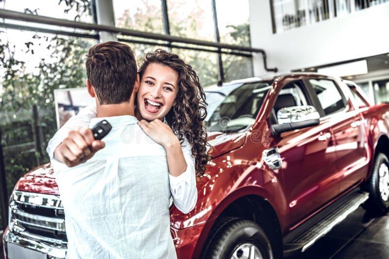 Spaß! Lächelnde Paare, die ihren neuen Schlüssel am Neuwagenausstellungsraum umarmen und halten stockfotografie