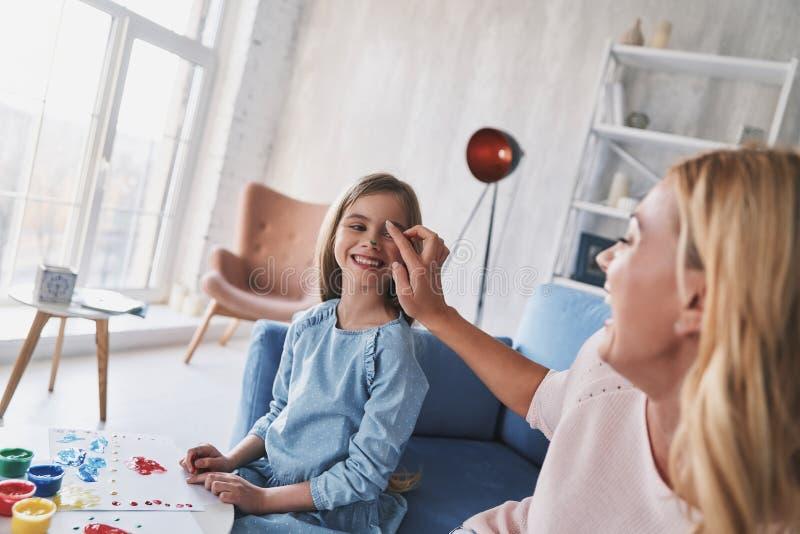 Spaß-Zeit zusammen Bemuttern Sie das Geben ihr der Tochtergesichtsfarbe und der Inspektion lizenzfreie stockfotografie