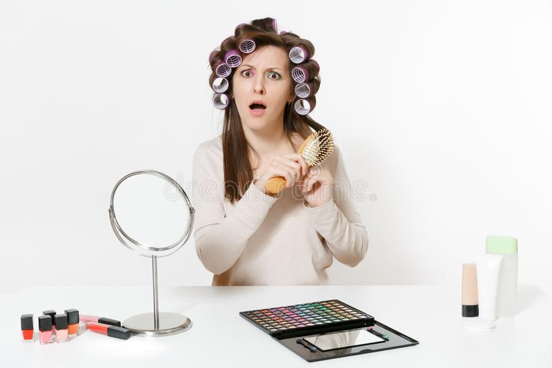 Spaßfrau mit Lockenwicklern unter Verwendung des Kämmens mit Kamm ihres Haares, bei Tisch sitzend, Make-up mit der gesetzten Gesi stockbilder