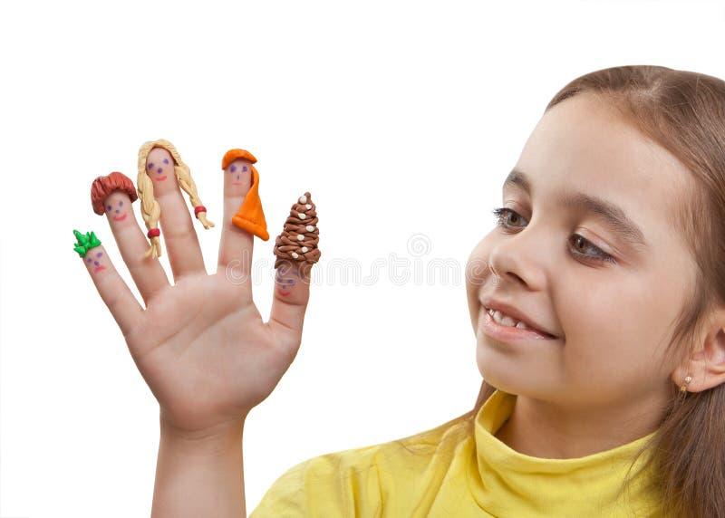Spaßmädchen, das nach einer Hand mit den gemalten Männern auf den Fingern in den Plasticineperücken sucht stockfoto