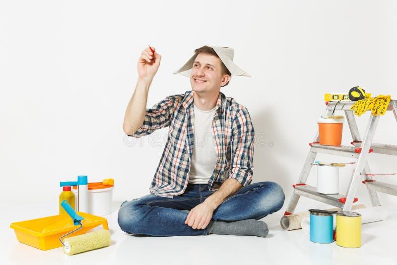 Spaßmann im Zeitungshut-Schreibensbleistift in einer Luft etwas auf Kopienraum Instrumente für die Erneuerungswohnung an lokalisi stockfotos