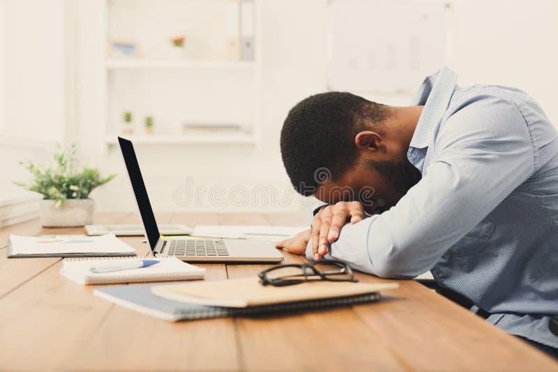 Spać przepracowywający się czarnego biznesmena z laptopem obrazy royalty free