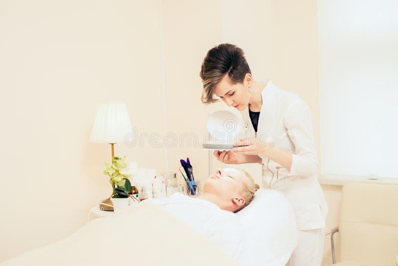 SPA γραφείο cosmetologist από cosmetology εξετάζει το δέρμα νέο κορίτσι που βρίσκεται στον καναπέ στοκ εικόνα