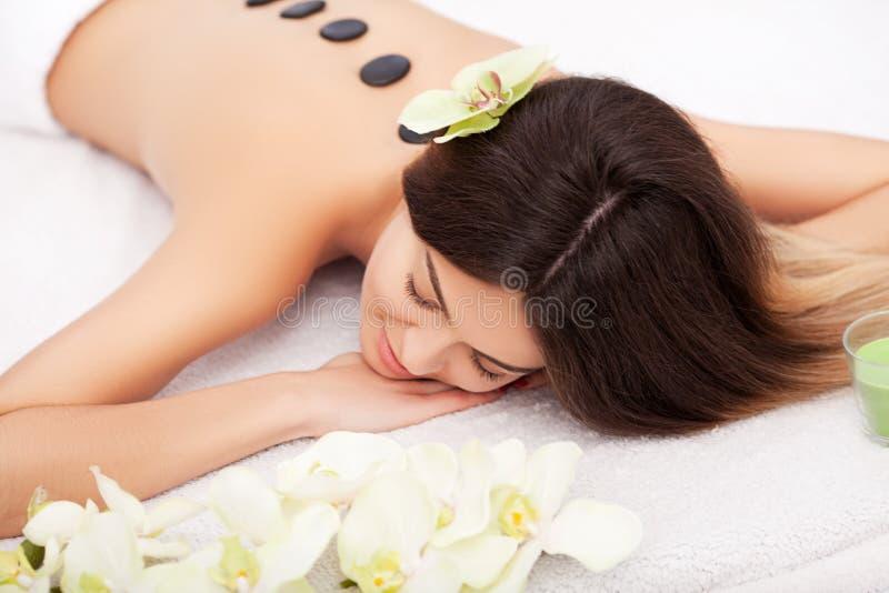 SPA Νέα γυναίκα που κάνει την καυτή θεραπεία πετρών Επαγγελματικό beauticia στοκ εικόνα