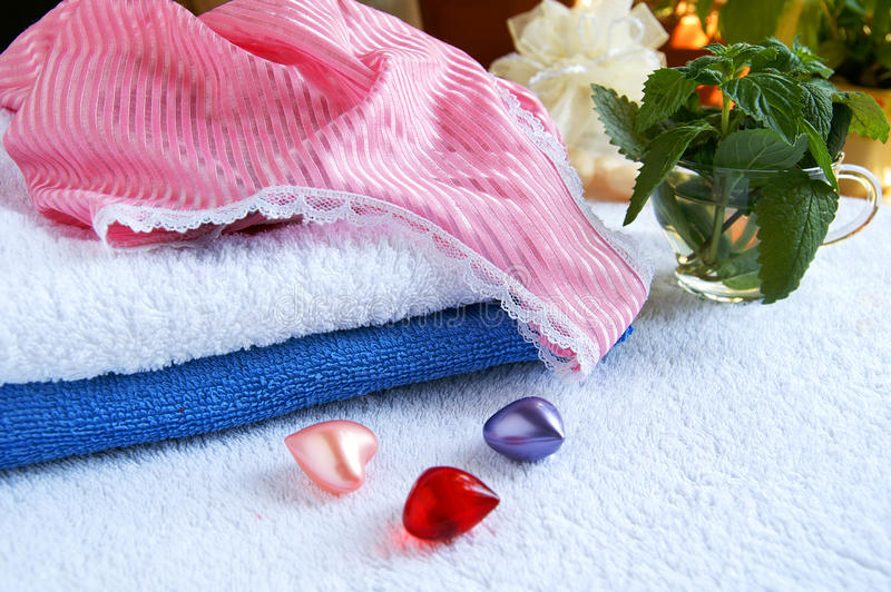 Spa accessories. Colorful towels, pajamas and bath aroma hearts in a spa-center stock photos