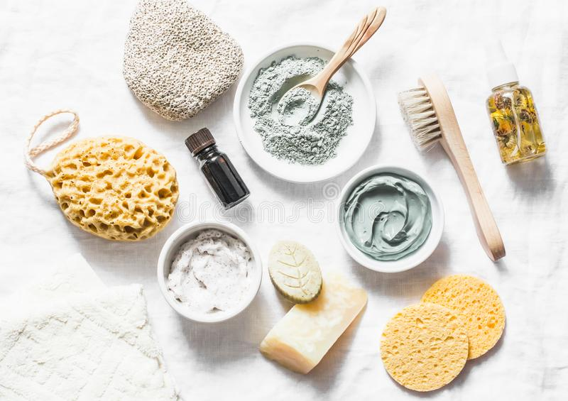 Spa accessories - nut scrub, sponge, facial brush, natural soap, clay face mask, pumice stone, essential oil on a light background. Top view. Healthy lifestyle royalty free stock images