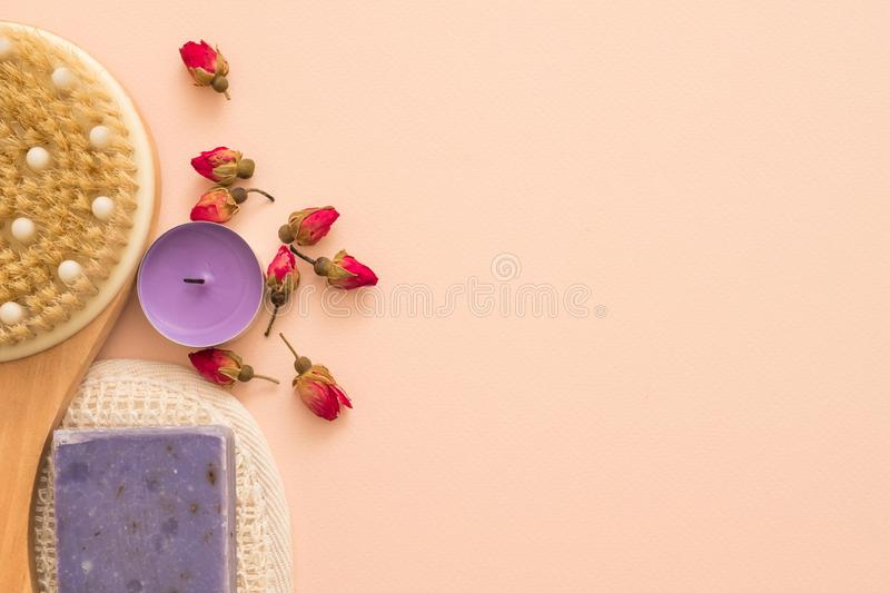 Spa aroma therapy relaxation tealight rose buds. Spa aroma therapy and relaxation. Wooden body brush, organic loofah, handmade soap, tealight and dried rose buds royalty free stock images