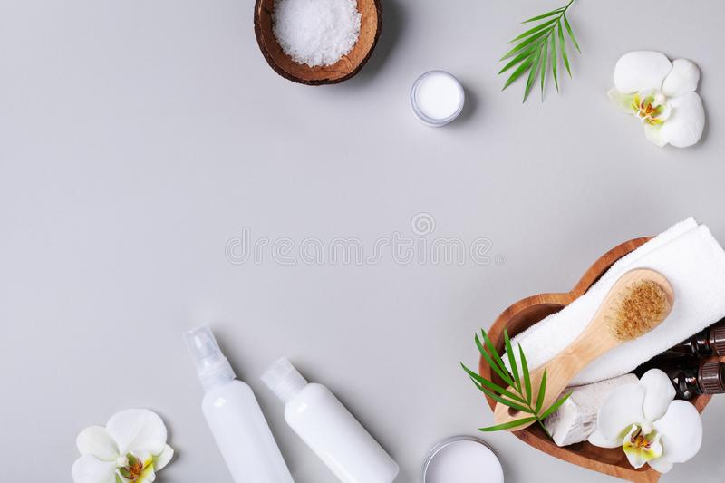 Spa, aromatherapy, beauty treatment and wellness background with massage brush, orchid flowers and cosmetic products. Top view and royalty free stock photo
