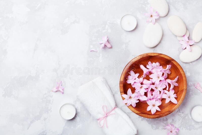 Spa aromatherapyen, skönhetbakgrund med massagekiselstenen, parfymerade blommor bevattnar och stearinljus på stentabellen från öv royaltyfria bilder