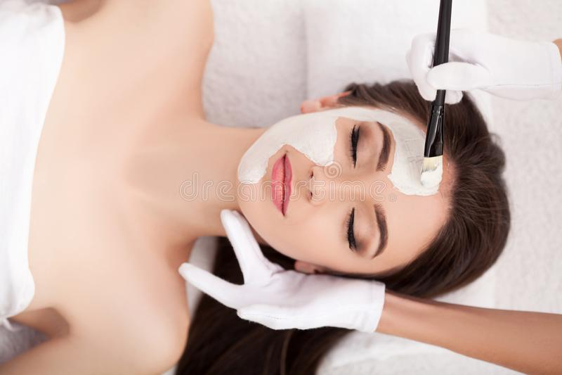 Spa. Attractive funny woman with a clay mask on her face. royalty free stock photography