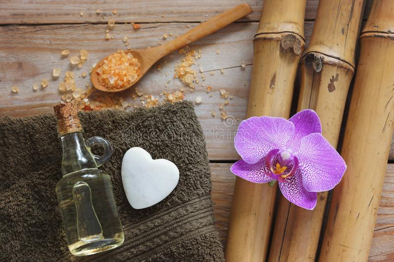 Spa background with bamboo, bath salt, massage oil, orchid flower, towel and stone in the shape of heart stock photos
