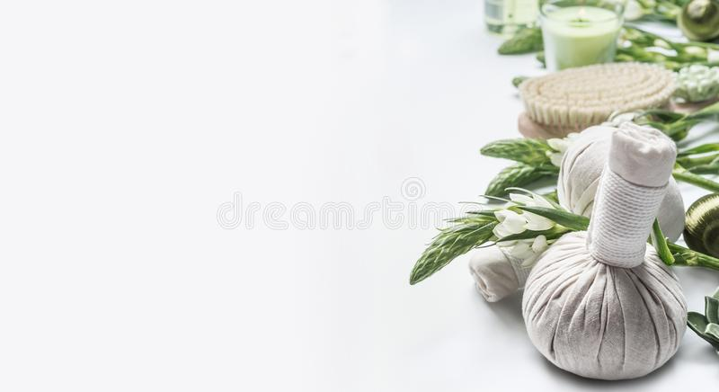 Spa background with massage herbal balls , green herbs and flowers on white. Beauty, healthy body care. And wellness concept stock photo
