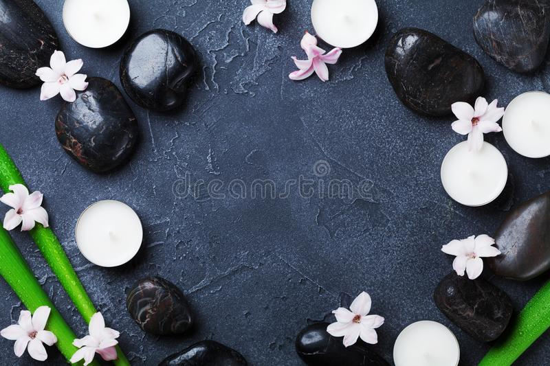 Spa background with massage pebble, green leaves, flowers and candles on black stone table top view. Aromatherapy, beauty. stock photography