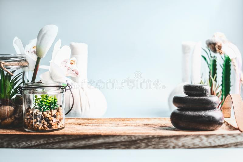 Spa background. Stack of hot stones setting, wellness equipment with succulent plants and white orchid flowers on table at light stock photography