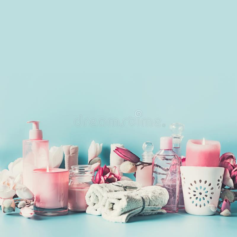 Spa background with towels, flowers, candles and body care cosmetics at light blue, top view with copy space. Beauty concept stock images