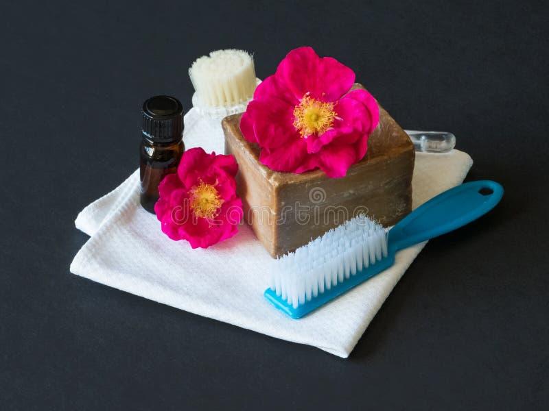 Spa baduppsättning Handgjord tvål, rosolja och rosblommor på en svart tabell arkivbild
