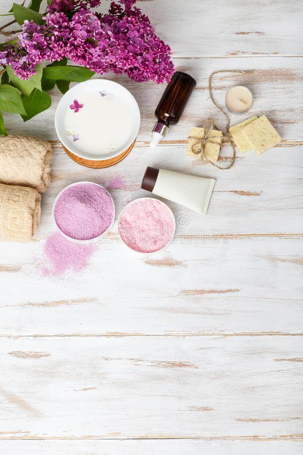 Spa and bath cosmetics with lilac flowers. Bath salt, soap, cream, oil, serum and towel rolls on wooden rustic background. Organic natural cosmetics. Fresh stock photos