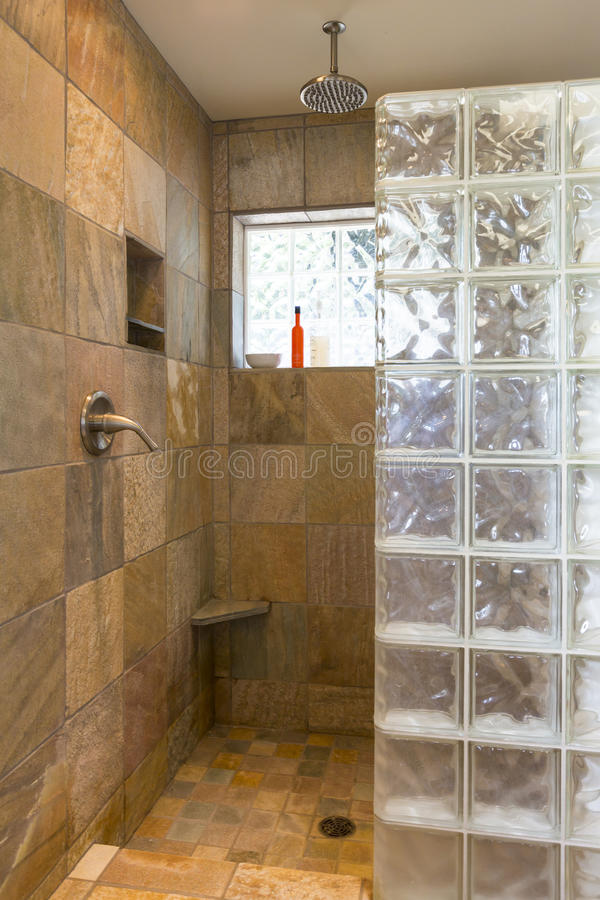 Spa bathroom shower area with stone tile and glass block walls in contemporary upscale home interior. Spa bathroom shower area with slate tile and glass block stock photography