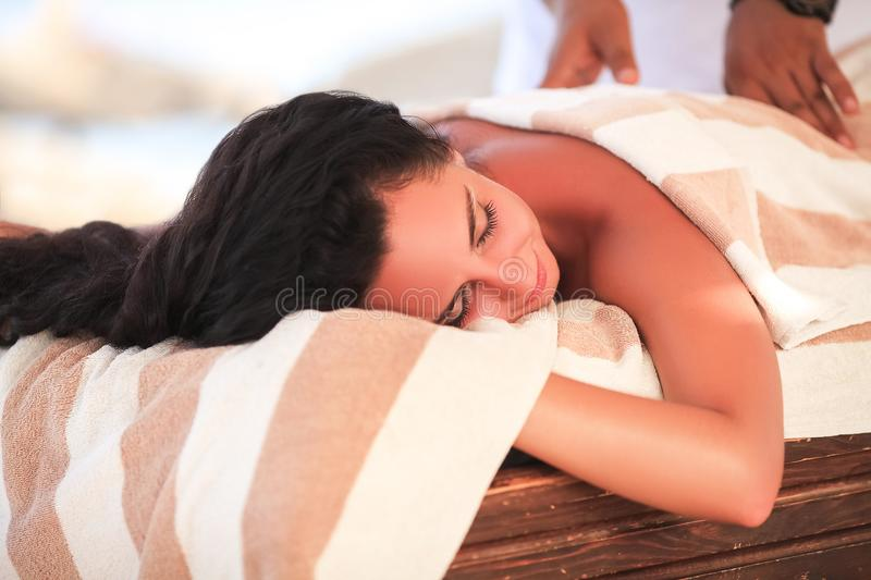 Spa. Beautiful woman get massage on sunny beach. Relax on vacations. stock photography