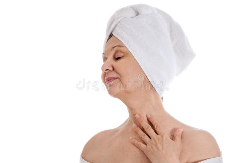 Spa and beauty concept. Aged good looking woman with white towel on her head. UK. Spa and beauty concept. Aged good looking woman with white towel on her head royalty free stock images