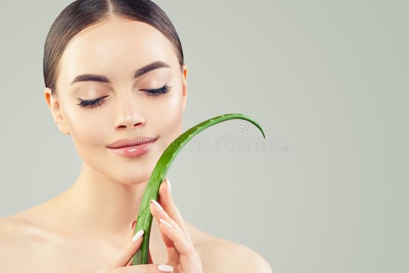 Spa beauty portrait of beautiful young woman with green aloe vera leaf. Skincare and facial treatment concept royalty free stock photography