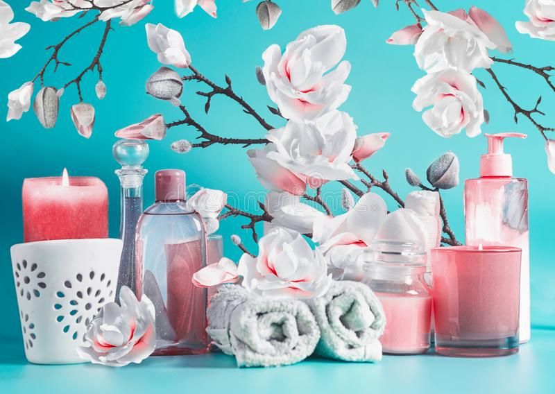 Spa beauty setting with tools: cream, towels, serum, burning candles, lotion , standing on pastel blue table at white pink blossom. Background. Salon wellness stock photography
