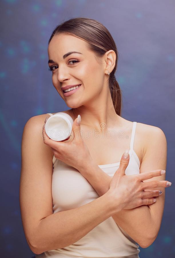 Spa beauty treatment Beautiful woman applying cosmetic cream treatment on her face and eyes. . royalty free stock photo